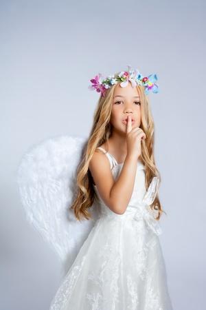 silence gesture: Angel children little girl sleeping finger in mouth gesture Stock Photo