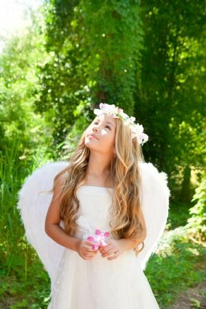 chicas guapas: Muchacha de los niños del ángel en bosque sostiene la flor en el cielo de la mano mirando