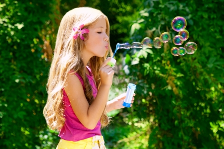 blowing bubbles: Children girl blowing soap bubbles in outdoor forest