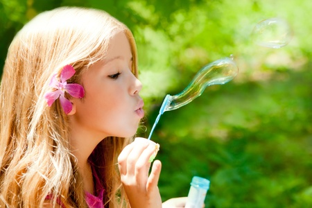 Children girl blowing soap bubbles in outdoor forest photo