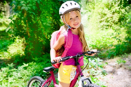 Children girl riding bicycle outdoor in forest smiling with helmet photo