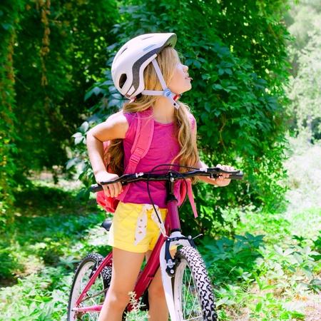 ni�os en bicicleta: Los ni�os chica montar bicicleta al aire libre en bosque sonriendo con casco Foto de archivo