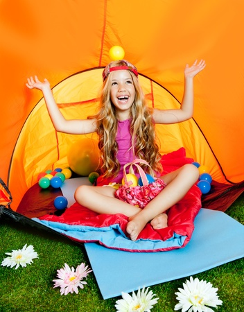 Girl playing with balls inside camping tent similing happy photo