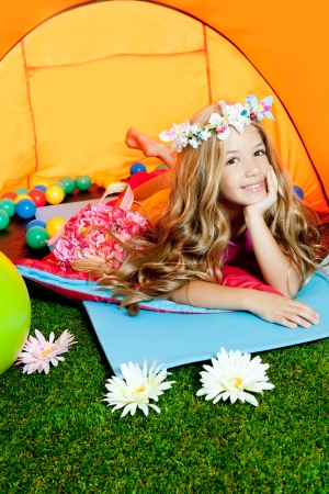 Children little girl lying in camping tent smiling with flowers crown photo
