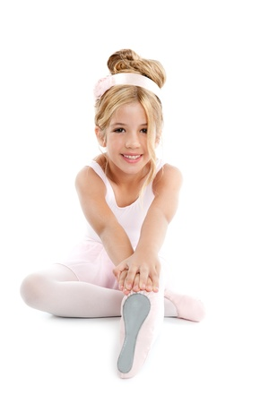 pretty young girl: Ballerina children dancer sitting on white Stock Photo
