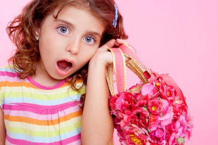surprised kid: brunette girl holding fashion spring flowers bag Stock Photo