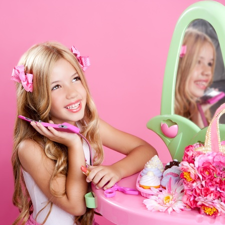 fashion doll: blond fashion doll girl talking with mobile phone in pink vanity Stock Photo