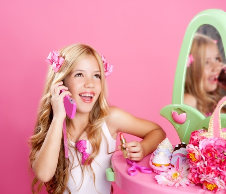 vintage children: blond fashion doll girl talking with mobile phone in pink vanity Stock Photo