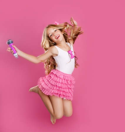 SINGING: blond singer star girl like fashion doll with mic jumping high Stock Photo