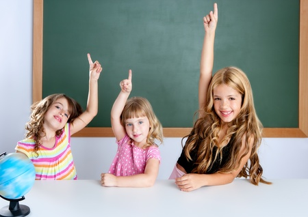 kids student clever girls group in classroom raising hand finger photo
