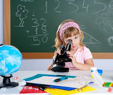 children little girl at school classroom with microscope in science class photo