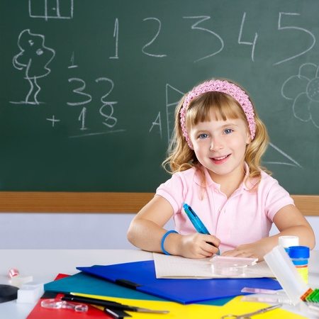 kids writing: happy similing student girl at school classroom Stock Photo