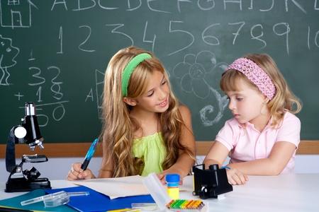 Niños ayudando: niños a estudiantes en aula ayudarse mutuamente en la mesa de la escuela