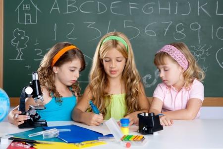 microscope: Grupo de niñas niños estudiantes en aula de escuela