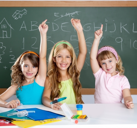 smart group of student kids at school classroom raising hand photo