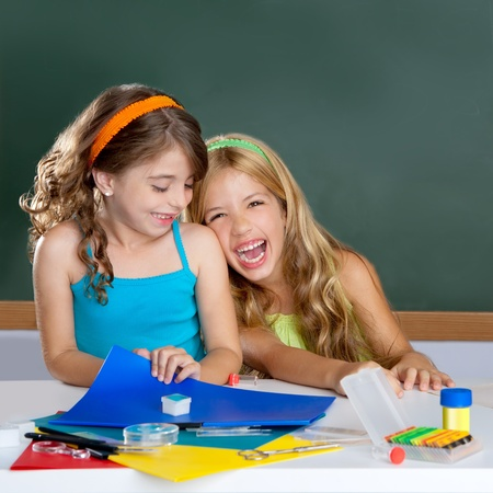 children laughing: happy laughing student girls group at school classroom desk