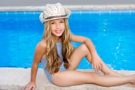 child swimsuit: blond children girl sittin in swimming pool border in summer vacation Stock Photo