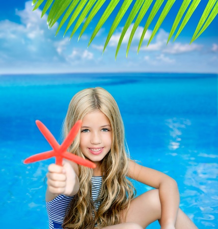 children blond girl in summer vacation tropical beach with starfish photo