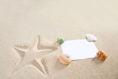 blank paper on white sand beach with shells and starfish print like a summer vacation concept photo