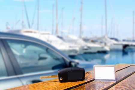 rental car: Car rental keys on wood table with blank paper in vacation boats Mediterranean marina Stock Photo
