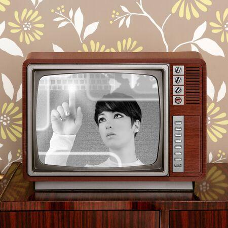television antigua: contraste futuro y retro en la pantalla del televisor vintage aparece una mujer futurista Foto de archivo