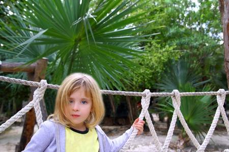 blond little girl on jungle rainforest adventure park over a rope bridge photo