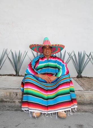 traje mexicano: Hombre sonriente de sombrero mexicano sentado con poncho en frente de cactus de agave
