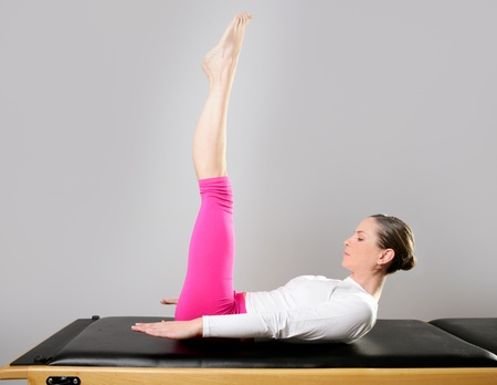 gym pilates woman in reformer doing yoga leg exercise photo