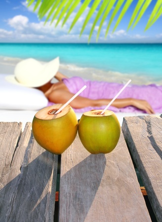 topical: coconut cocktails with a woman sun tanning in topical Caribbean beach Stock Photo