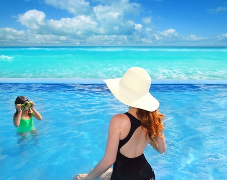 blue swimming pool with direct caribbean view rear motherview and goggles daughter in background photo