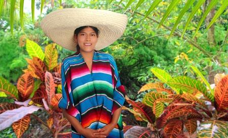Latina mujer hispana mexicana con sombrero y poncho en la selva de la selva photo