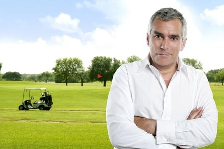 golfing: senior golfer man portret in het groen natuurlijk buiten met kar achtergrond