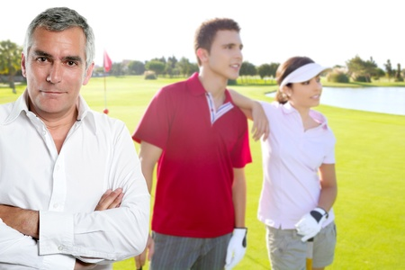 senior golfer man portrait in green course withyoung couple in background photo