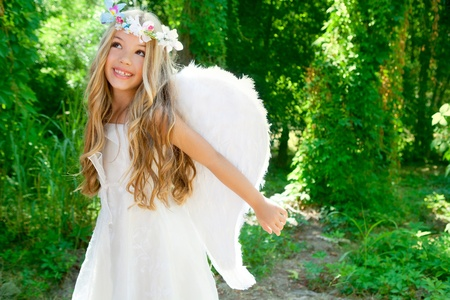 Angel children girl open arms in forest with white wings and flowers crown