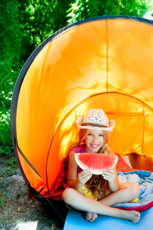 children girl in camping tent eating watermelon slice at forest photo