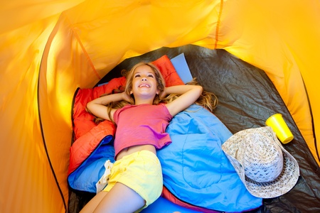 Children girl lying on camping tent floor in vacation photo