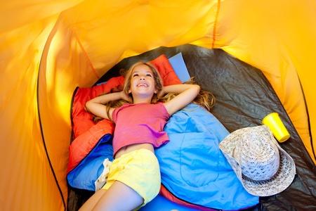 sleeping bag: Children girl lying on camping tent floor in vacation