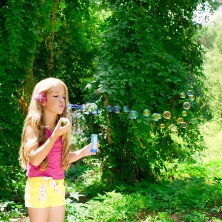 blow: I bambini ragazza che soffia bolle di sapone nella foresta outdoor Archivio Fotografico