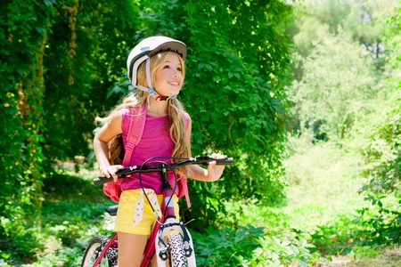 riding: Children girl riding bicycle outdoor in forest smiling with helmet