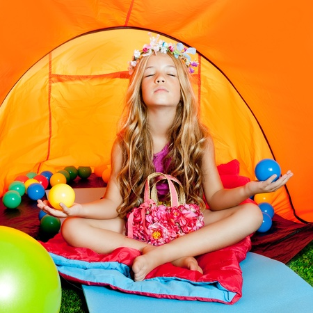 Children girl in camping tent practicing yoga open arms and balls