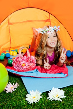 Children with peace hand sign lying indoor of camping tent photo