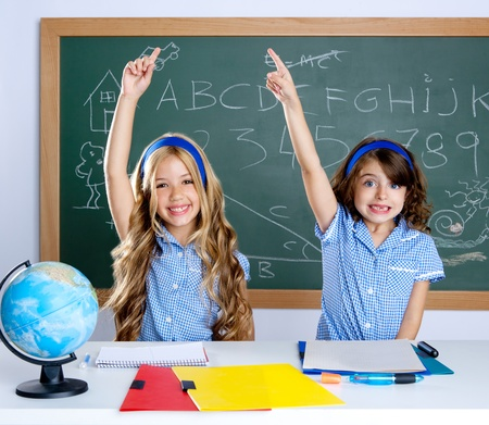 clever: smart students in classroom raising hand with blackboard