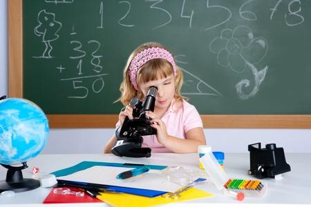 microscope: los niños niña en aula de escuela con microscopio en clase de Ciencias