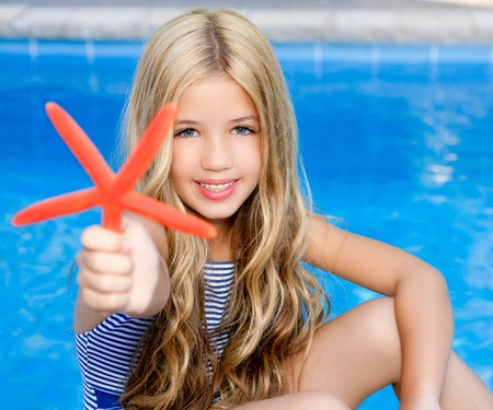 little girl swimsuit: children blond girl in summer vacation  pool with starfish Stock Photo