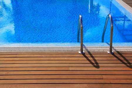 pool deck: blue swimming pool with teak wood flooring deck summer vacation concept Stock Photo