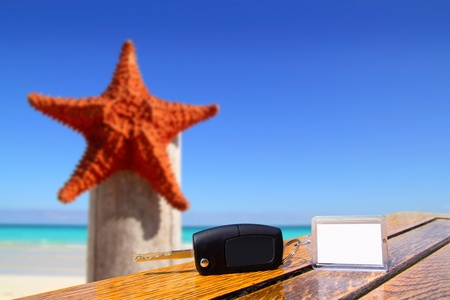 rent car: Car rental keys on wood table with blank paper in vacation with starfish of Caribbean beach Stock Photo
