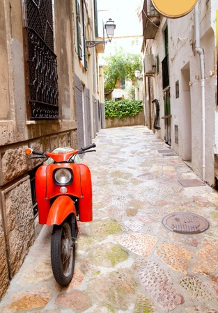 palma: Mediterranean street with old retro red scooter in Palma de Mallorca Spain