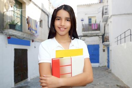 Brunette student young teen latin girl holding books white mediterranean village photo