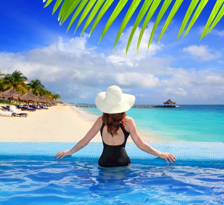 riviera: black swimsuit woman rear view in a pool with direct view to tropical Caribbean sea Stock Photo