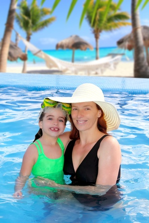 mexican girl: mother and daughter hug in a pool with direct view to Caribbean tropical beach
